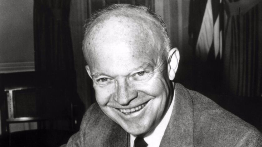 President Dwight D. Eisenhower, who would soon begin his second four year term in office, poses at his White House desk on Nov. 8, 1956.