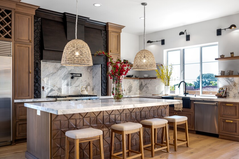 The geometric pattern on the front of the island and the spice racks flanking the range and hood were handcarved from alder.