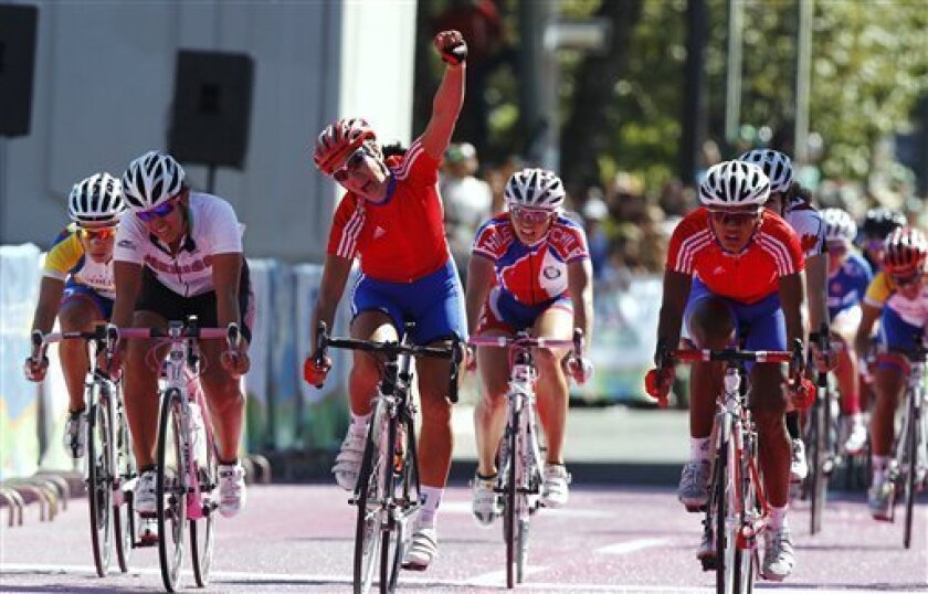 Cuba's Yudelmis Dominguez raises her hand as she crosses the finish line, taking the bronze, during the women's cycling road race at the Pan American Games in Guadalajara, Mexico, Saturday, Oct. 22, 2011. Teammate Yumari Gonzalez, who won the silver, is at right. Cuba's Arlenis Sierra, not in pictu