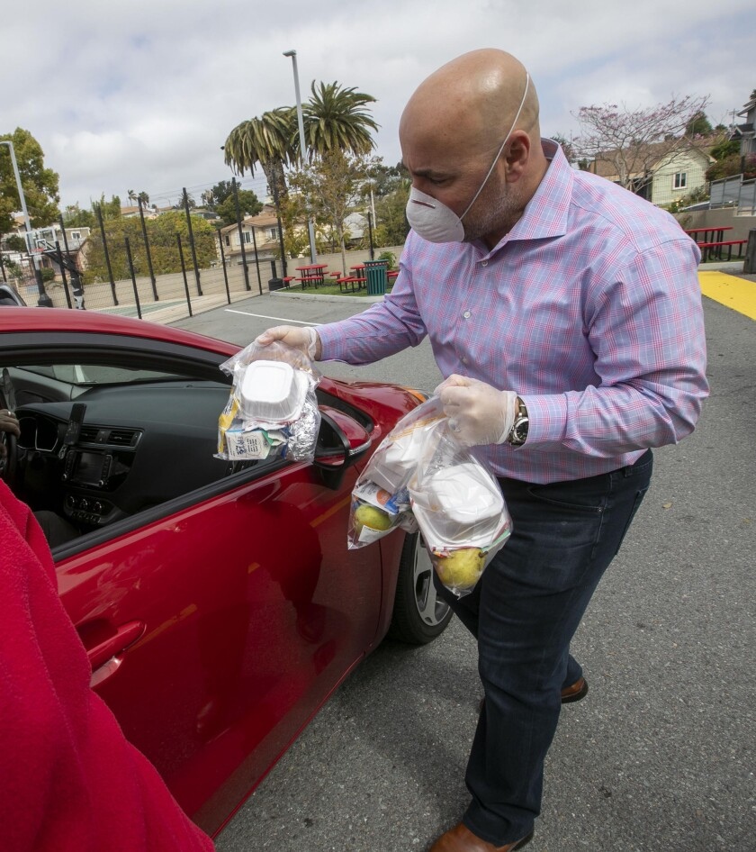 Andy Trakas, an Aztecs kicker from 1989-92, hands out meals Thursday to families affected by coronavirus impacts. He's the principal of Albert Einstein Academies.