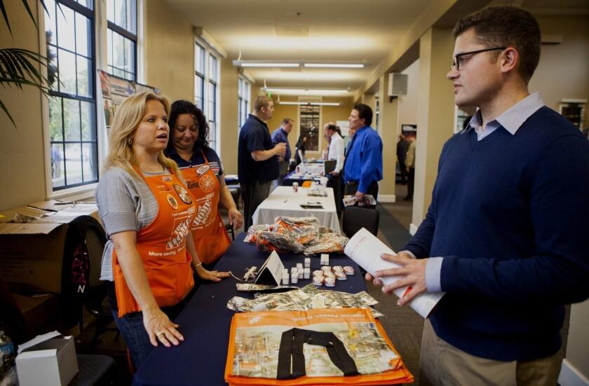 Home Depot Inc. representatives speak with a job seeker at the Recruit Military veterans job fair in San Diego.