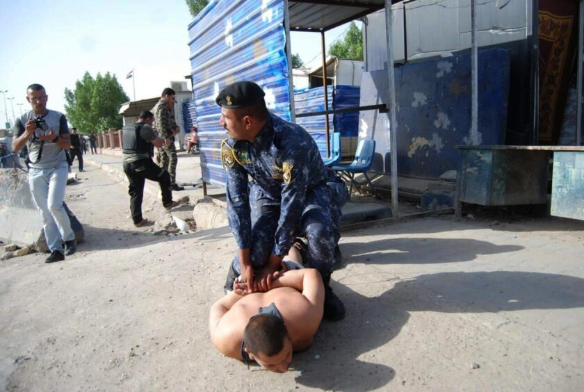 In this image released by Iraq's Federal Police on Wednesday, May 25, 2016, policeman Saad Ali Thabit detains a would-be suicide bomber at a checkpoint north of Baghdad's Kadhimiyah neighborhood. Thabit is being honored as a hero by Iraqi officials and on social media. Closed Circuit video of Thabi