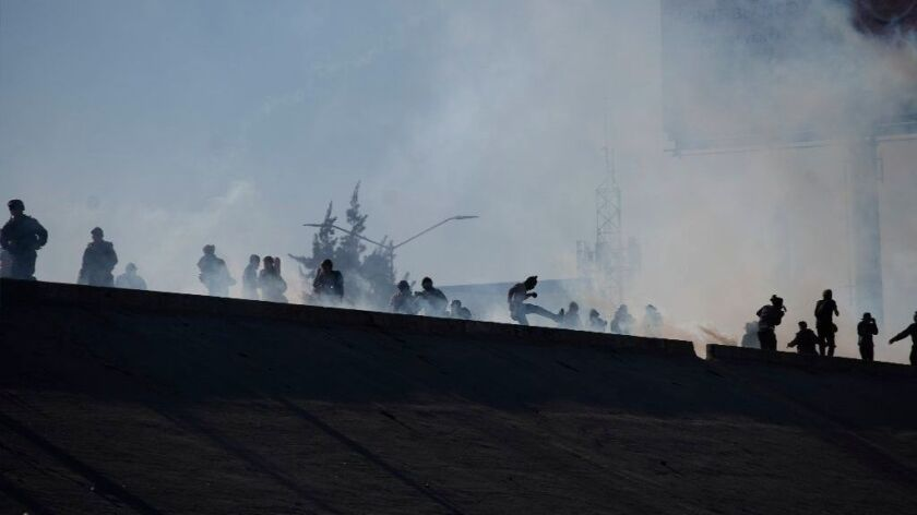 Migrants run from tear gas launched by U.S. agents at part of the border with Mexico in Tijuana on Nov. 25.