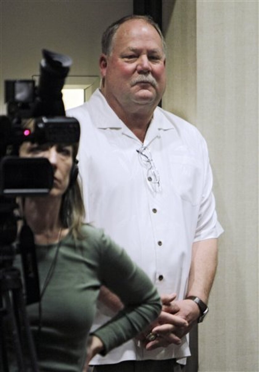Cleveland Browns president Mike Holmgren watches from the back of the room as first-round draft pick Phillip Taylor holds a news conference at the NFL football team's headquarters in Berea, Ohio Friday, April 29, 2011. (AP Photo/Mark Duncan)