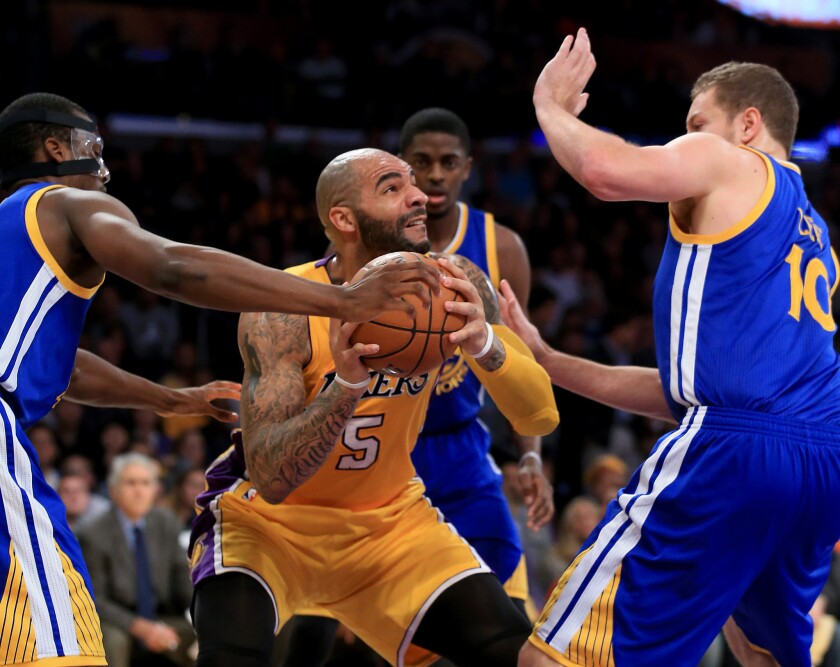 Carlos Boozer draws a crowd of Golden State defenders during the first quarter of the Lakers' 115-105 win over the Warriors.