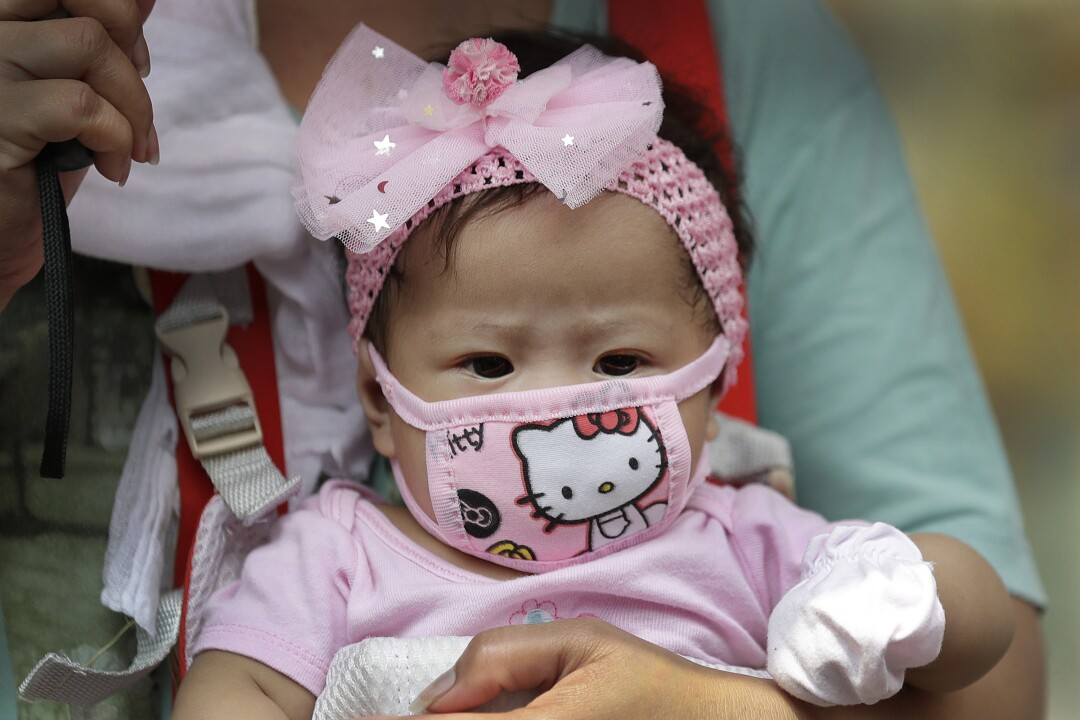A baby wears a Hello Kitty facial mask in Manila.