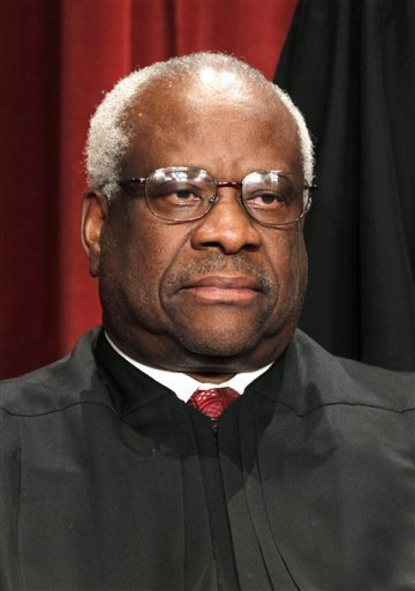 FILE - In this Oct. 8, 2010 file photo, Associate Justice Clarence Thomas is seen during the group portrait at the Supreme Court Building in Washington. Liberals and Democrats in Congress want Justice Thomas off the health care case. Conservative interest groups and Republican lawmakers say it's Justice Elena Kagan who should sit it out. Neither justice is budging — the right decision, according to many ethicists and legal experts. (AP Photo/Pablo Martinez Monsivais, file)
