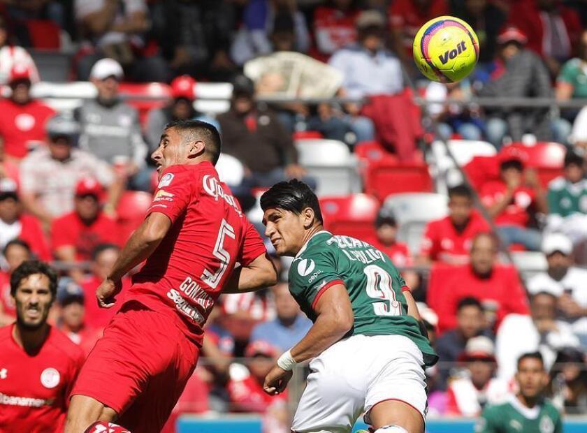 El jugador de Toluca Osvaldo González (i) y Alan Pulido (d) de Chivas disputan el balón hoy, domingo 7 de enero de 2018, durante el juego correspondiente a la jornada 1 del torneo mexicano de fútbol celebrado en el estadio Nemesio Diez, en la ciudad de Toluca (México). EFE