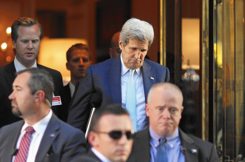 U.S. Secretary of State John F. Kerry, rear right, leaves his hotel for a meeting with Iranian Foreign Minister Mohammad Javad Zarif in Vienna.