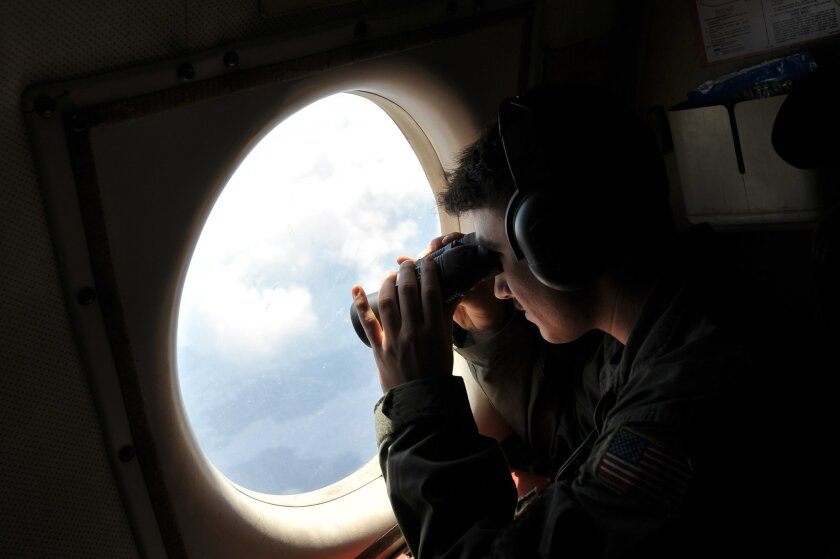 U.S. Navy LT. JG Dylon Porlas uses binoculars to look through the window of a U.S. Navy Lockheed P-3C Orion patrol aircraft from Sigonella, Sicily, Sunday, May 22, 2016, searching the area in the Mediterranean Sea where the Egyptair flight 804 en route from Paris to Cairo went missing on May 19. Search crews found floating human remains, luggage and seats from the doomed EgyptAir jetliner Friday but face a potentially more complex task in locating bigger pieces of wreckage and the black boxes vital to determining why the plane plunged into the Mediterranean. (AP Photo/Salvatore Cavalli)