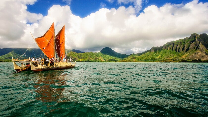 The Hokulea, a modern-day replica of an ancient voyaging canoe, passes the Kualoa Coast of Oahu early in its around-the-world sailing.