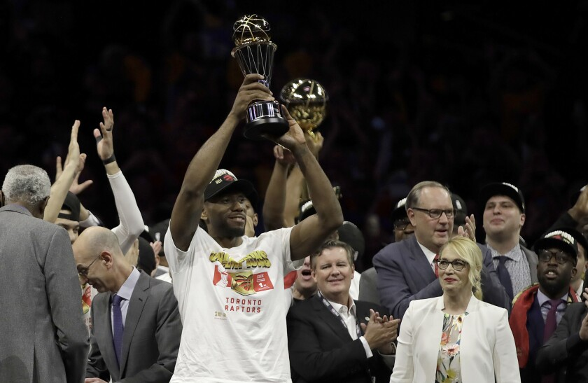 Kawhi Leonard last June hoisting his second NBA Finals MVP trophy, surrounded by a crowd.