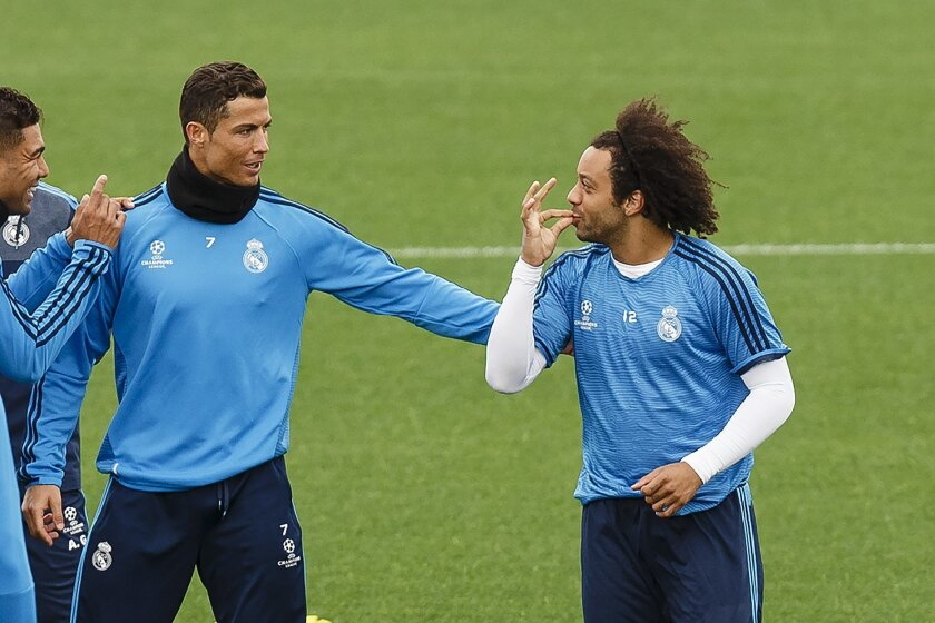Real Madrid players Casemiro, left, Cristiano Ronaldo, center, and Marcelo speak during a training session in Valdebebas stadium, Spain, Monday, May 2, 2015. Real Madrid will face Paris Saint-Germain in a Group stage of Champion's League Group A soccer match on Tuesday.(AP Photo/Daniel Ochoa de Olz