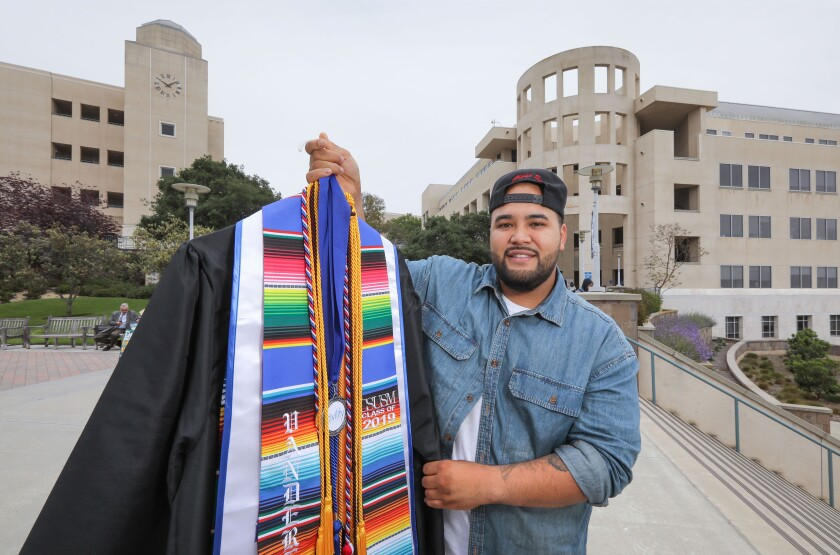 Portrait of California State University San Marcos graduating senior and commencement speaker Stephen Vandereb with his gown and honors he'll wear during the ceremony.