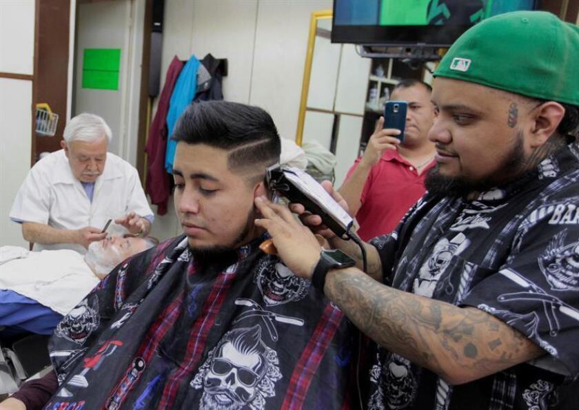 Fotografía fechada el 28 de marzo de 2018 que muestra al barbero Francisco Hernández (d) mientras corta el pelo a un cliente en una barbería de la colonia Tabacalera, en Ciudad de México (México). EFE