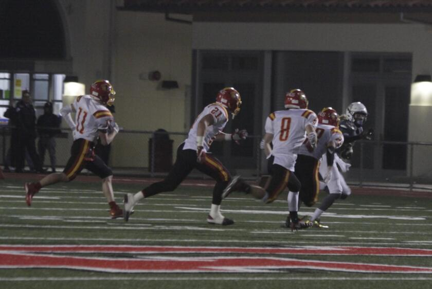 Several Oakdale Mustangs chase a Bishop's School Knight, as he makes his way down the field with the ball.