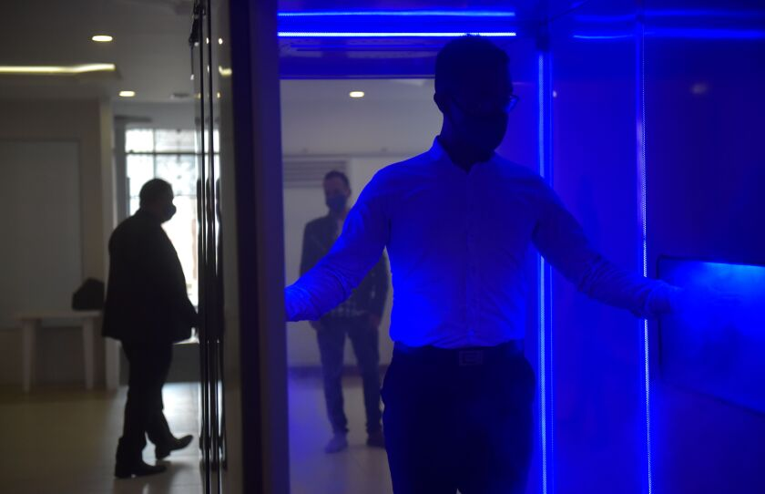 A man passes through a device that uses ultraviolet light.