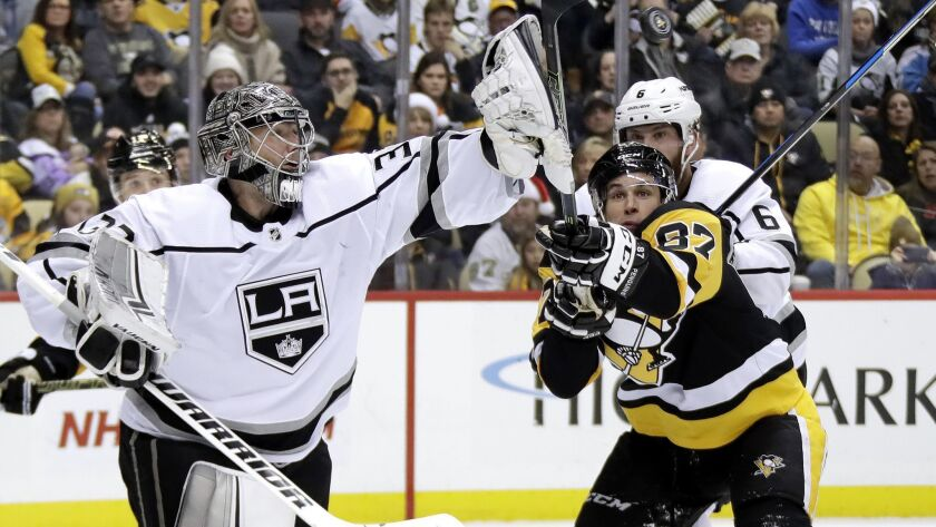 Kings goaltender Jonathan Quick (32) swats the puck out of the air before Pittsburgh Penguins' Sidney Crosby (87) can get his stick on it during the second period on Saturday in Pittsburgh.