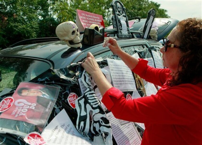 Philomena Johnson, a delegate from Little Village Academy, decorates her vehicle to highlight the need for increased social services in schools before attending a meeting of the Chicago Teachers Union delegates Sunday, Sept. 16, 2012 in Chicago. Hundreds of CTU delegates are expected to review a pr