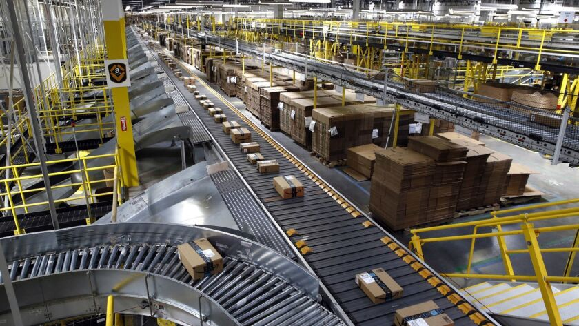 FILE- In this Aug. 3, 2017, file photo, packages ride on a conveyor system at an Amazon fulfillment