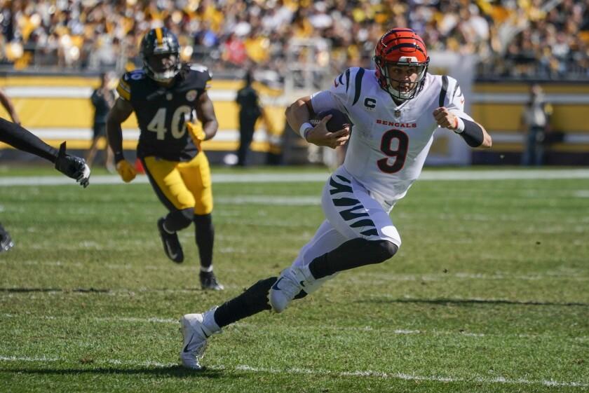 Cincinnati Bengals quarterback Joe Burrow (9) scrambles for a first down against the Pittsburgh Steelers during the second half an NFL football game, Sunday, Sept. 26, 2021, in Pittsburgh. (AP Photo/Gene J. Puskar)