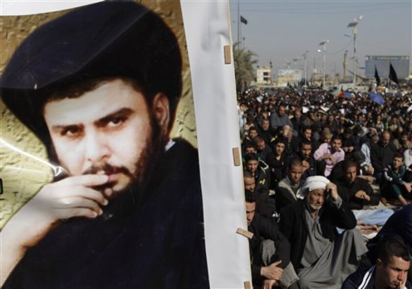 A poster depicting radical Shiite cleric Muqtada al-Sadr at left as followers gather for Friday prayers in the Sadr City neighborhood in Baghdad, Iraq, Friday, Jan. 7, 2011. Al-Sadr, who led several Shiite uprisings against American forces in Iraq before going into exile in neighboring Iran almost four years ago, returned to Iraq on Wednesday. (AP Photo/Karim Kadim)