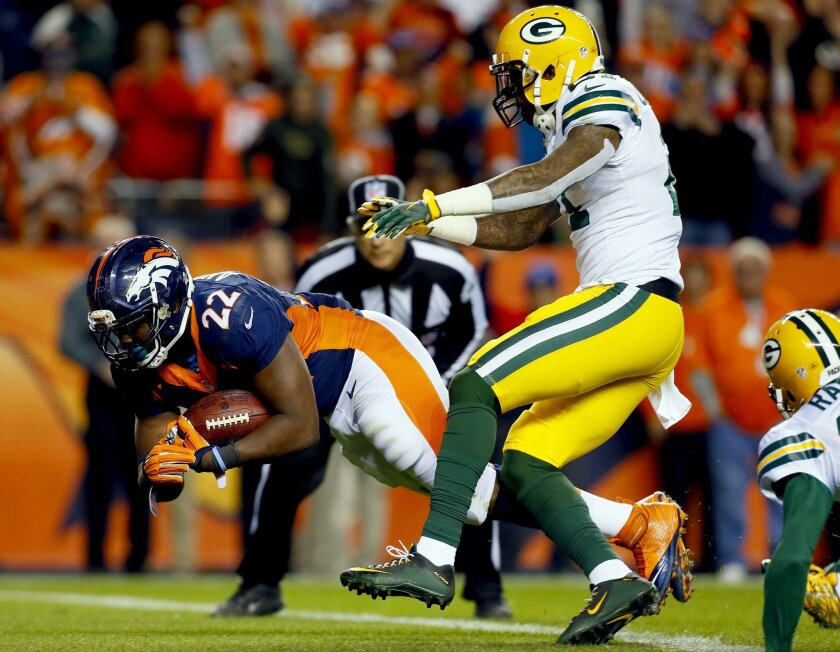 Denver Broncos running back C.J. Anderson (22) scores a touchdown as Green Bay Packers free safety Ha Ha Clinton-Dix (21) defends during the second half of an NFL football game, Sunday, Nov. 1, 2015, in Denver. (AP Photo/Jack Dempsey)