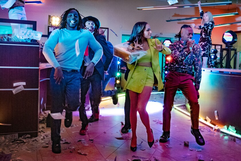 A group of four people dance on a dance floor with dollar bills strewn all over