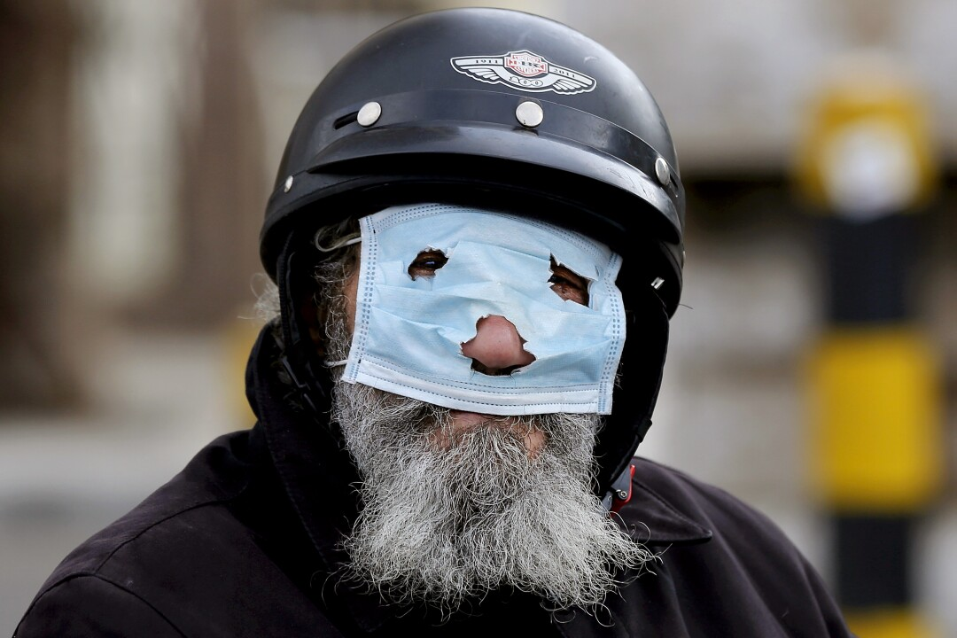 LEBANON: A bearded man covers his face with a punched-out surgical mask in Beirut.