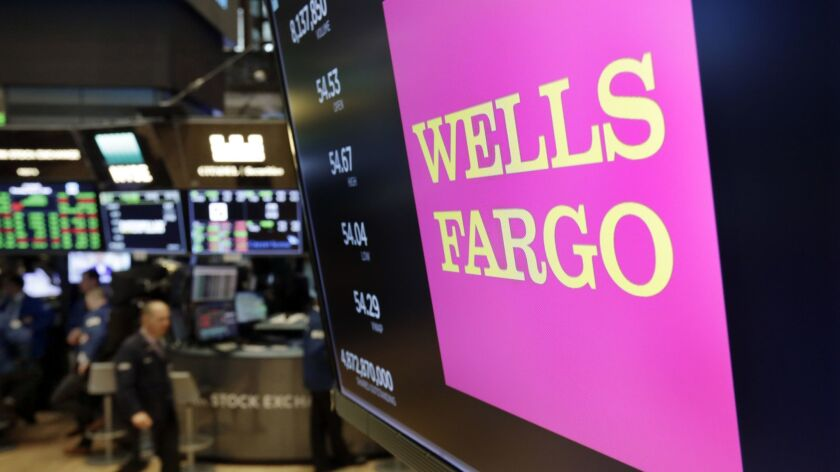 FILE - This May 17, 2018 file photo shows the Wells Fargo logo above a trading post on the floor of