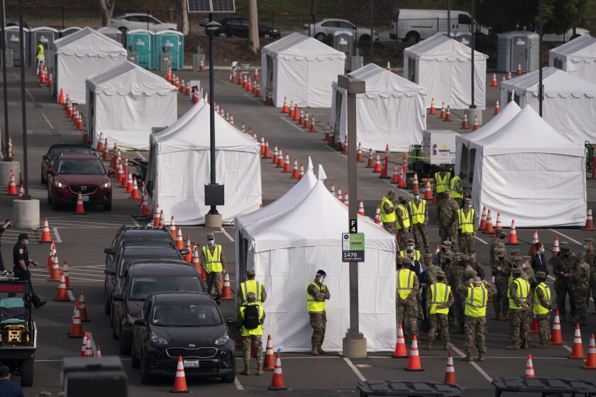 Motorists wait to get their COVID-19 vaccine at a federally-run vaccination site set up on the campus of California State University of Los Angeles in Los Angeles, Tuesday, Feb. 16, 2021. (AP Photo/Jae C. Hong)
