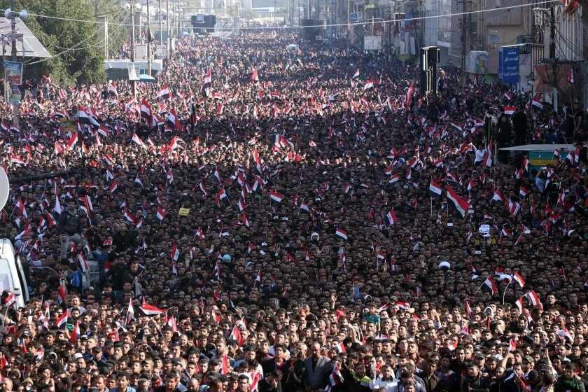 Followers of Iraq's influential Shiite cleric Muqtada al-Sadr stage a demonstration, calling for governmental reforms, as they wave national flags in Tahrir Square in Baghdad, Iraq, Friday, Feb. 26, 2016. (AP Photo/Hadi Mizban)