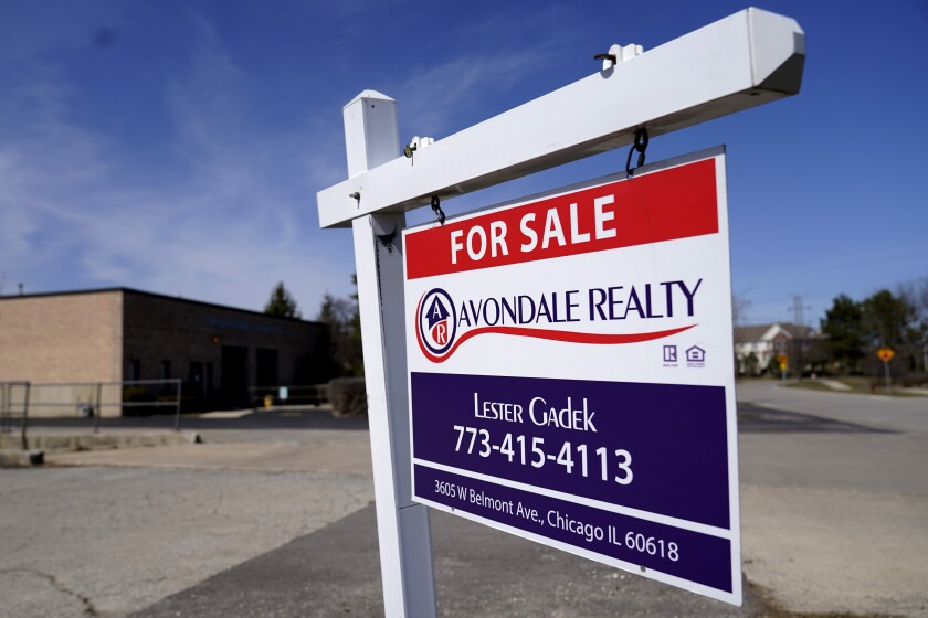 """A """"For Sale"""" sign stands along side a building lot in Wheeling, Ill., Sunday, March 21, 2021. Sales of new homes plunged 18.2% in February as severe winter weather in many parts of the country and a lack of supply took a toll on the housing industry. (AP Photo/Nam Y. Huh)"""
