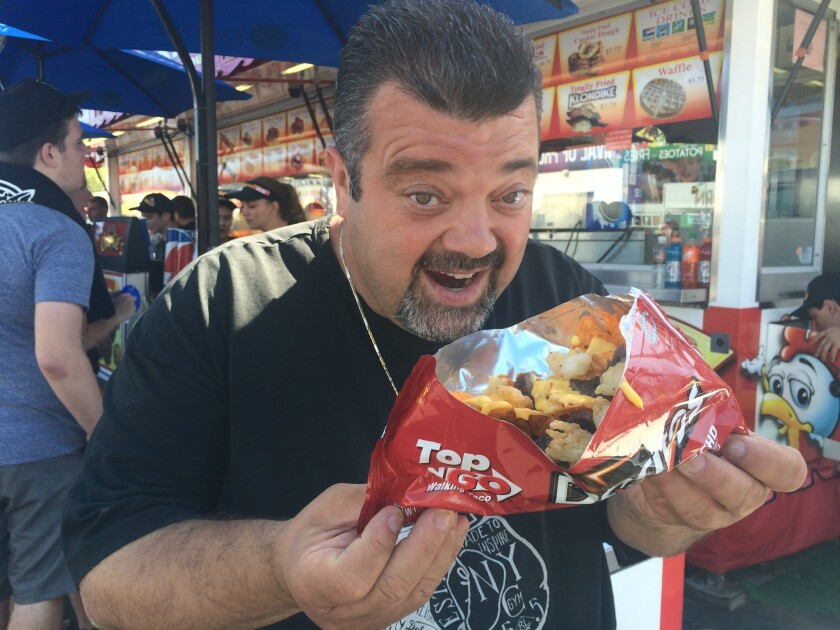 Charlie Boghosian, owner of Chicken Charlie's, holds an order of his creation, steak and lobster nachos, on July 16 at the Orange County Fair.