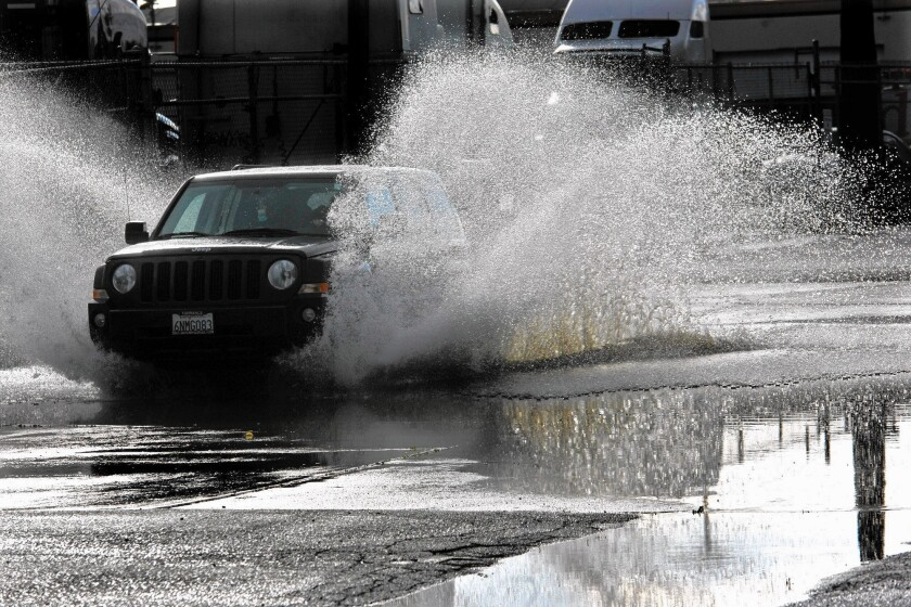 A car wades through a flooded street in El Segundo. Last week's rainstorms added 6 billion gallons of water to San Gabriel Valley's drought-parched reservoirs.