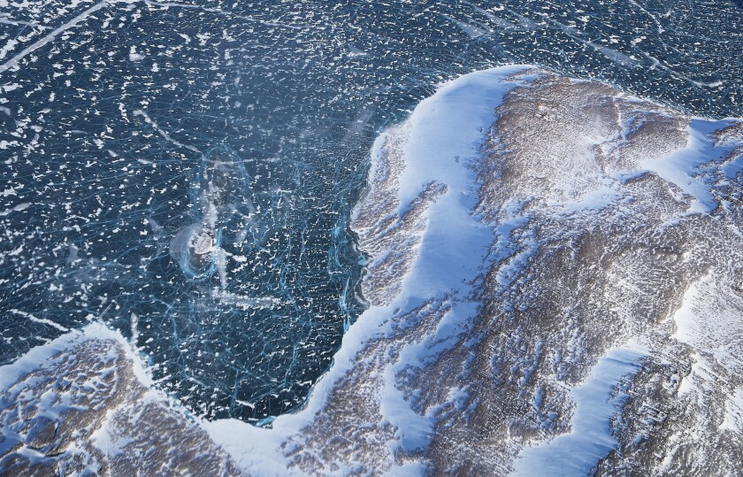 Sea ice meets land as seen from NASA's Operation IceBridge research aircraft along the Upper Baffin Bay coast above Greenland.