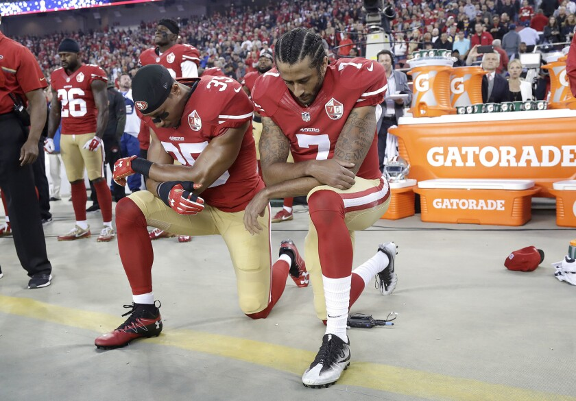 San Francisco 49ers safety Eric Reid (35) and quarterback Colin Kaepernick (7) kneel during the national anthem before a game against the Rams in Santa Clara.