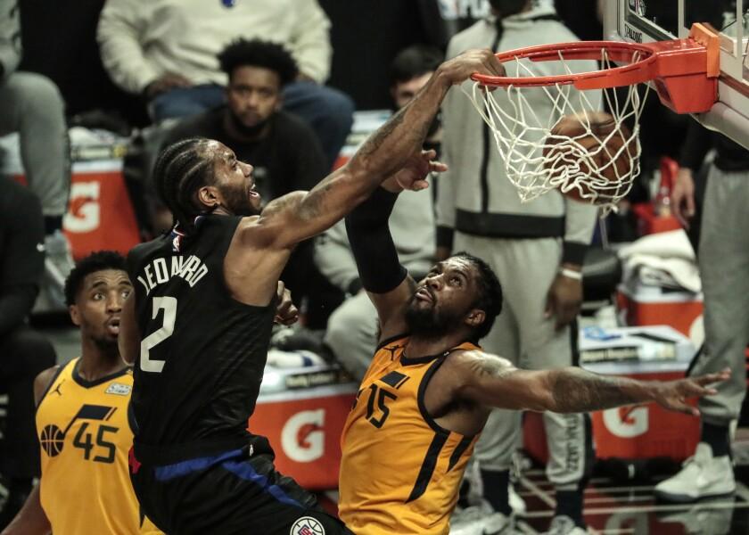 Clippers forward Kawhi Leonard dunks over Jazz center Derrick Favors