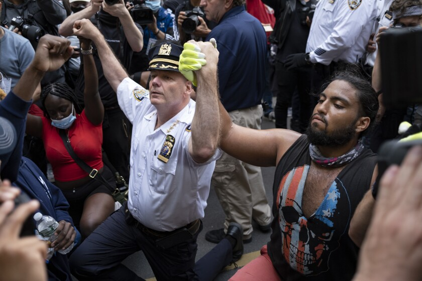 NYPD Chief of Department Terence Monahan kneels with protesters Monday in New York.