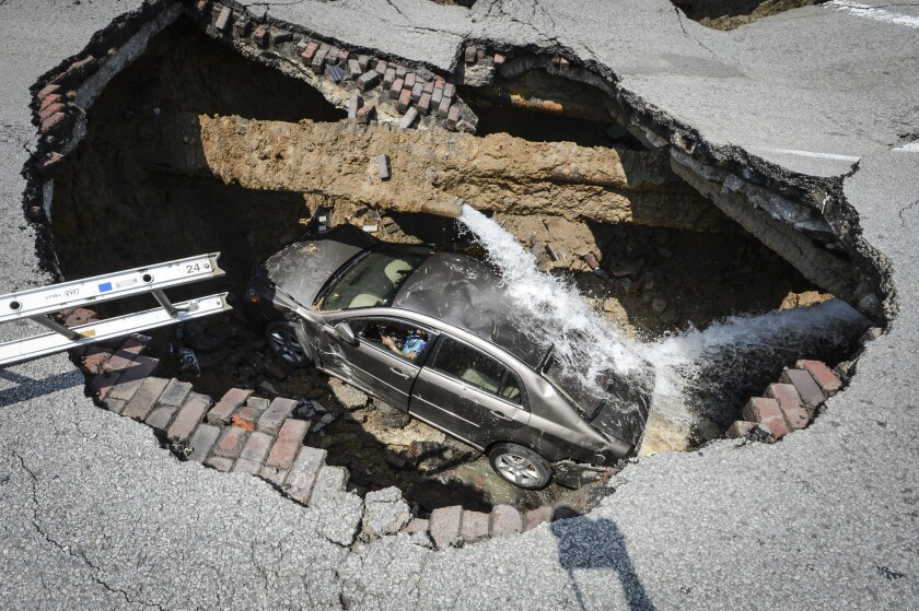 A car lies at the bottom of a sinkhole caused by a broken water line in Toledo, Ohio, on Wednesday. Police say the driver, Pamela Knox of Toledo, was shaken up and taken to a hospital as a precaution.