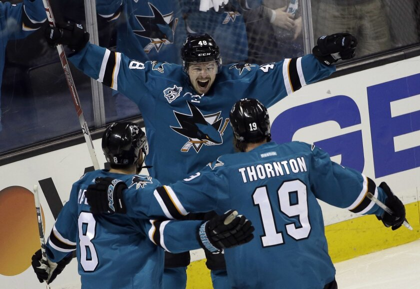 San Jose Sharks' Tomas Hertl (48) celebrates his goal with teammates Joe Thornton (19) and Joe Pavelski (8) during the third period in Game 3 of the NHL hockey Stanley Cup Western Conference finals against the St. Louis Blues on Thursday, May 19, 2016, in San Jose, Calif. San Jose won 3-0. (AP Photo/Marcio Jose Sanchez)