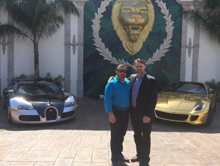 Two men pose in front of luxury cars