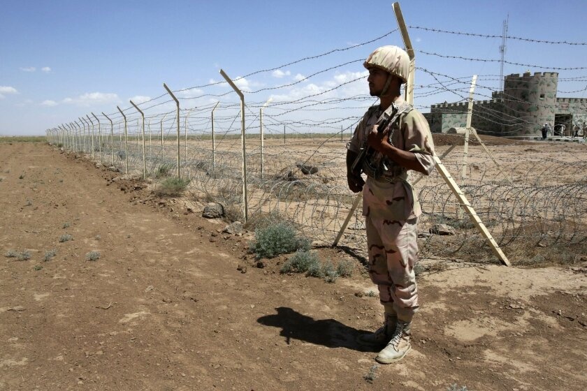 In this Sunday, June 1, 2014 photo, an Iranian border guard patrols Iran's Dogharoun border with Afghanistan, near Taibad in eastern Iran. In the face of Afghanistan's unprecedented boom in opium production, neighboring Iran is trying to baton down its border to slow down smuggling, building moats, walls and other large-scale projects. Iran spent more than $26 million last year alone on the border projects which also include large embankments, new border posts and lengths of barbed wire along parts of its 2,000-kilometer (1,200-mile) border with Afghanistan and Pakistan. (AP Photo/Vahid Salemi)