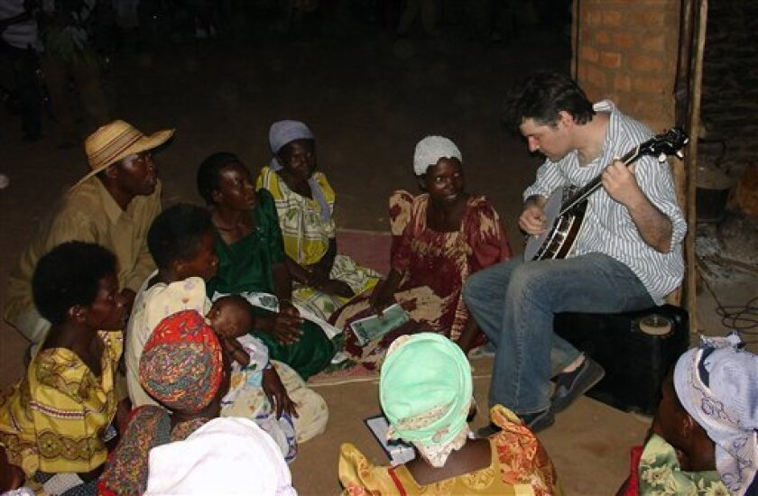 "Banjo virtuoso Bela Fleck is shown performing for the Nakisenyi Women's Group in Uganda.  His 2008 film and album, ""Throw Down Your Heart,"" chronicled Fleck's journey to Uganda, Tanzania, Gambia and Mali to visit and play music with local artists."