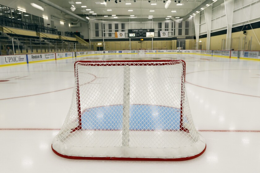 A hockey goal on the ice in a local public skating rink