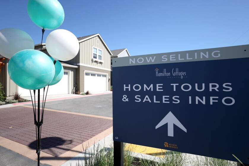 A sign is posted in front of new homes for sale at Hamilton Cottages last September in Novato, Calif.