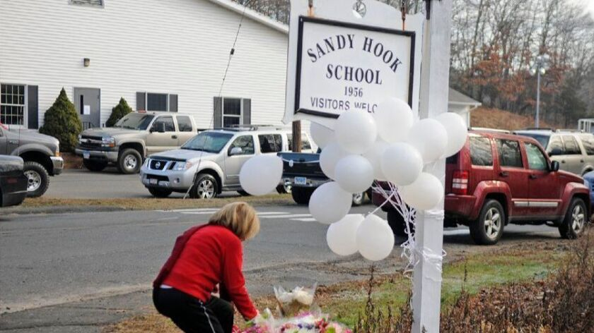 A woman places a memento below a sign for Sandy Hook School where others have placed flowers the day after the Sandy Hook Elementary School massacre in December 2012.