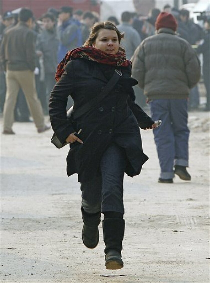 Karen Patterson of Canada, wife of Chinese artist Wu Yuren, runs as she arrives for her husband's trial at the Wenyuhe Court in Beijing, China Wednesday, Nov. 17, 2010. Wu was detained and charged after he helped organize protests near Tiananmen Square against some urban development plans in the 79