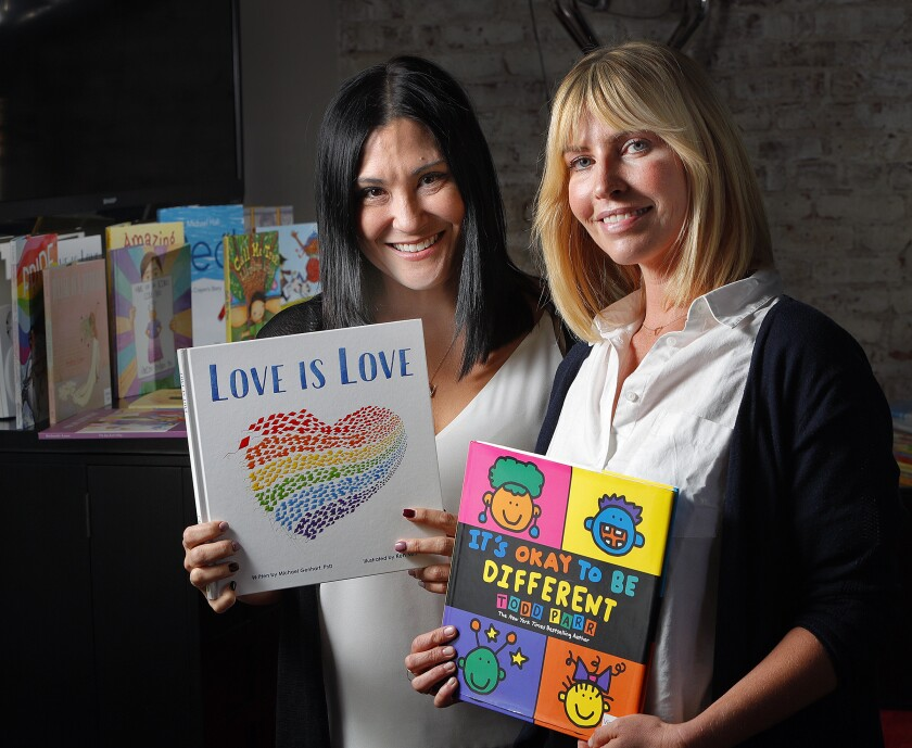 Gender Nation co-founders Keiko Feldman of La Crescenta and Morgan Walsh of Toluca Lake hold some of the LGBTQ-friendly books they are distributing through Juris Productions Inc. in Pasadena. The duo made a large donation to the Glendale Unified School District.