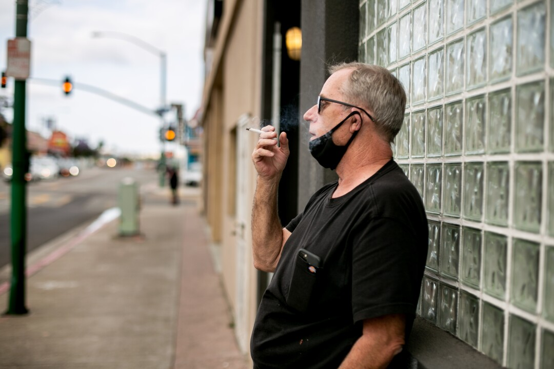 Bill Lutzius, owner of Brooklyn Bar & Grill takes a drag from a cigarette outside the bar.